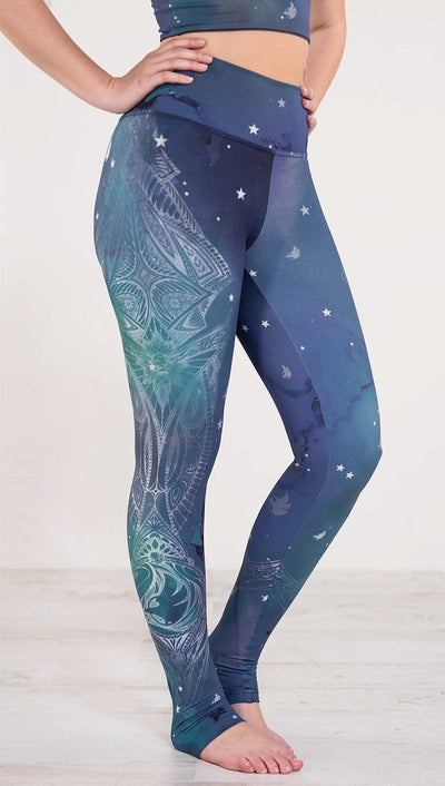 Right side view of model wearing a blue and green galaxy themed athleisure leggings with white henna inspired art running along the right side of the leg