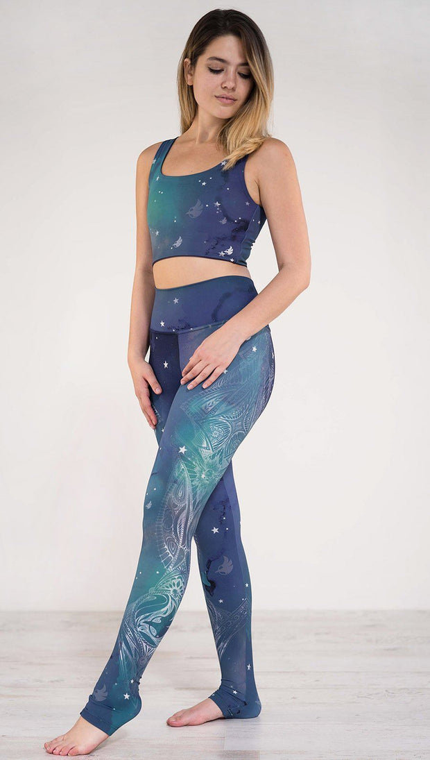 Model pointing toe wearing a blue and green galaxy themed athleisure leggings with white henna inspired art running along the left side of the leg