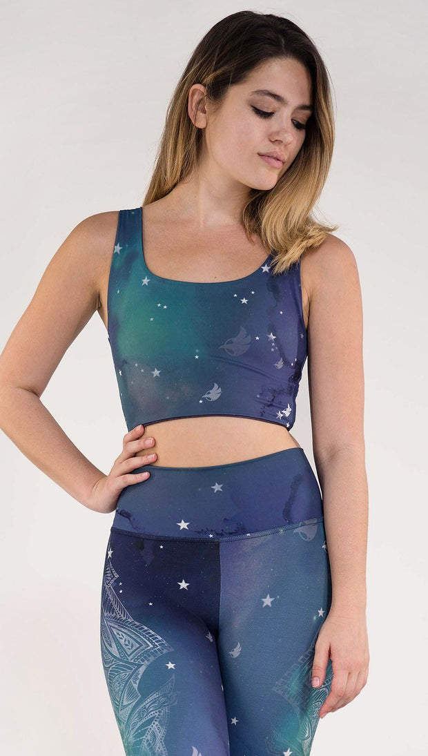 Model wearing a blue and green galaxy themed reversible crop top called Galactic Azure on this side