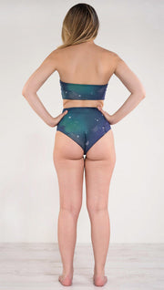 Back view of model wearing a blue and green galaxy themed reversible high waist bikini bottom called Galactic Azure on this side