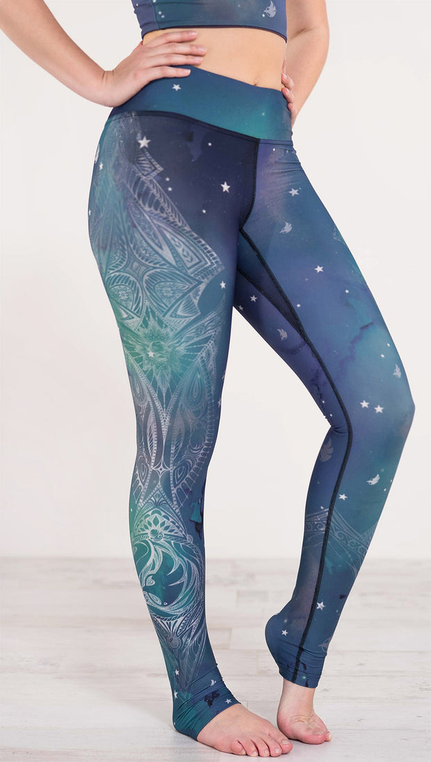 Right side of blue and green galaxy themed triathlon leggings with white henna inspired art running along the right side of the leg