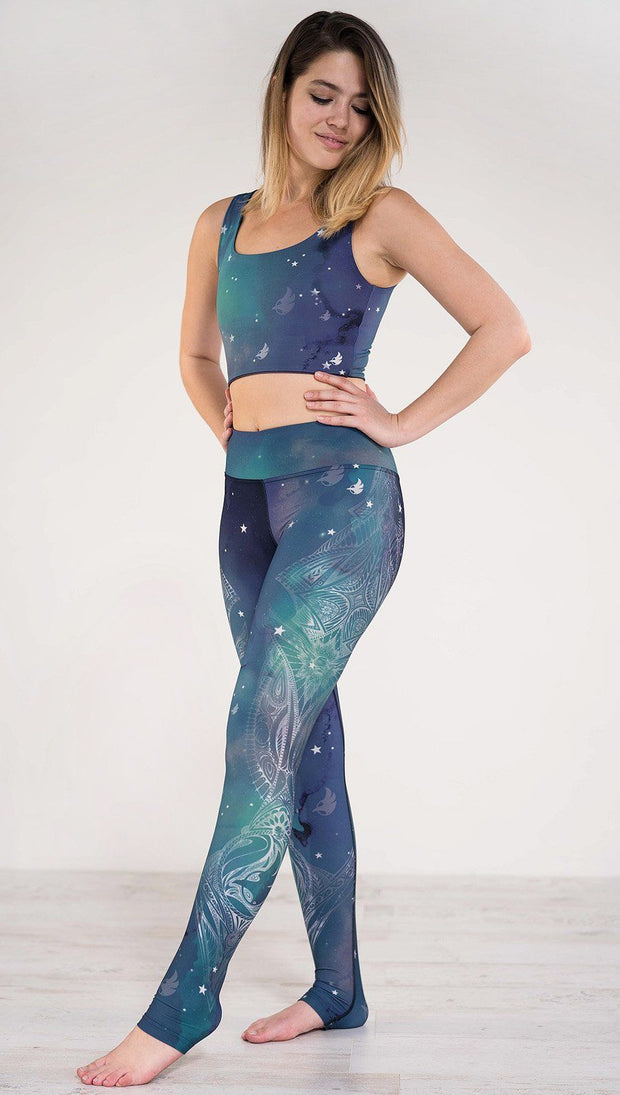 Model pointing toe wearing a blue and green galaxy themed triathlon leggings with white henna inspired art running along the left side of the leg
