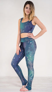 Left side view of model wearing a blue and green galaxy themed triathlon leggings with white henna inspired art running along the left side of the leg