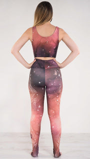 Back side view of model wearing a red, orange and purple galaxy themed athleisure leggings
