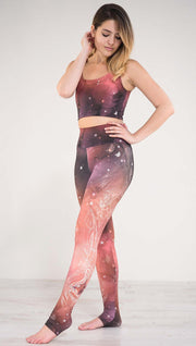 Model pointing toe wearing a red, orange and purple galaxy themed athleisure leggings with white henna inspired art running along the left side of the leg