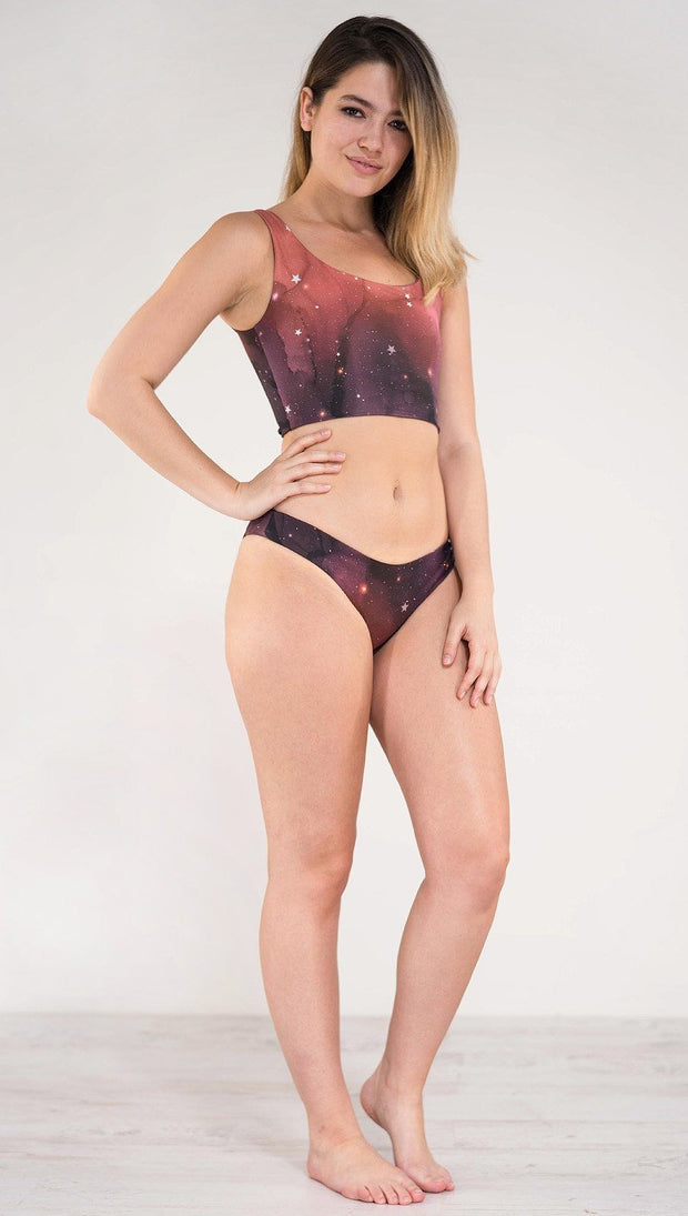Right side view of model wearing reversible low rise red, orange and purple galaxy themed bikini bottom called Galactic Solar Flare on this side