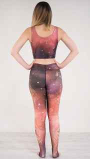 Back side view of model wearing a red, orange and purple galaxy themed leggings