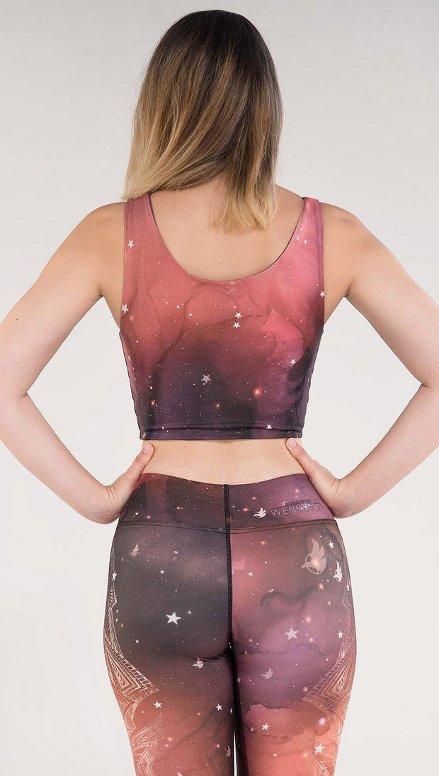 Back side view of model wearing a red, orange and purple galaxy themed reversible crop top called Galactic Solar Flare on this side