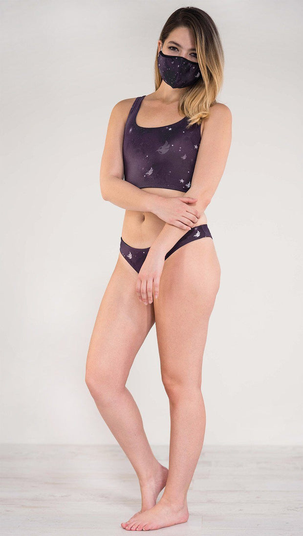 Left side view of model wearing a purple galaxy themed low rise reversible bikini bottom called Galactic Moon Dust on this side