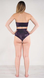 Back view of model wearing a purple galaxy themed reversible high waist bikini bottom called Galactic Moon Dust on this side