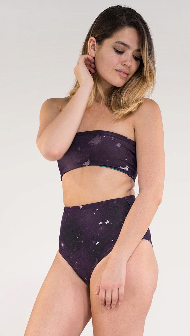 Model wearing a purple galaxy themed reversible high waist bikini bottom called Galactic Moon Dust on this side