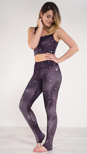 Left side view of model wearing purple galaxy themed triathlon leggings with white henna inspired flowers running along the left side of the leg