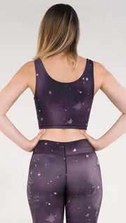 Back view of model wearing a purple galaxy themed reversible crop top called Galactic Moon Dust on this side