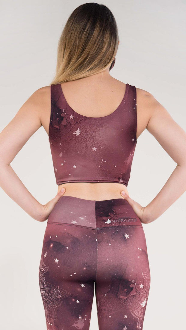 Back side view of model wearing a merlot color galaxy themed reversible crop top called Galactic Merlot on this side