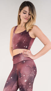 Left side view of model wearing a merlot color galaxy themed reversible crop top called Galactic Merlot on this side