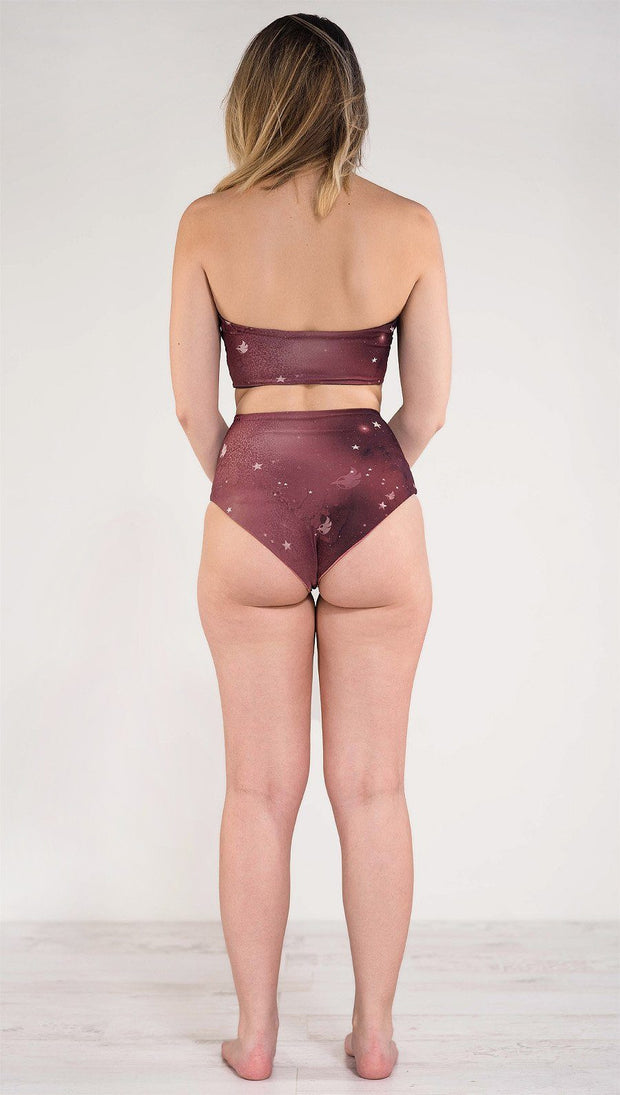 Back side view of model wearing reversible high waist merlot color galaxy themed bikini bottom called Galactic Merlot on this side