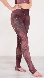 Model pointing toe wearing a merlot color galaxy themed triathlon leggings with white henna inspired flowers running along the right side of the leg