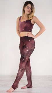 Model pointing toe wearing a merlot color galaxy themed triathlon leggings with white henna inspired flowers running along the left side of the leg