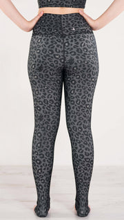 Back side view of model wearing the reversible charcoal leopard print athleisure leggings in the colors gray and black