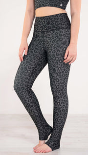 Enhanced view of model wearing reversible charcoal leopard print athleisure leggings in the colors gray and black