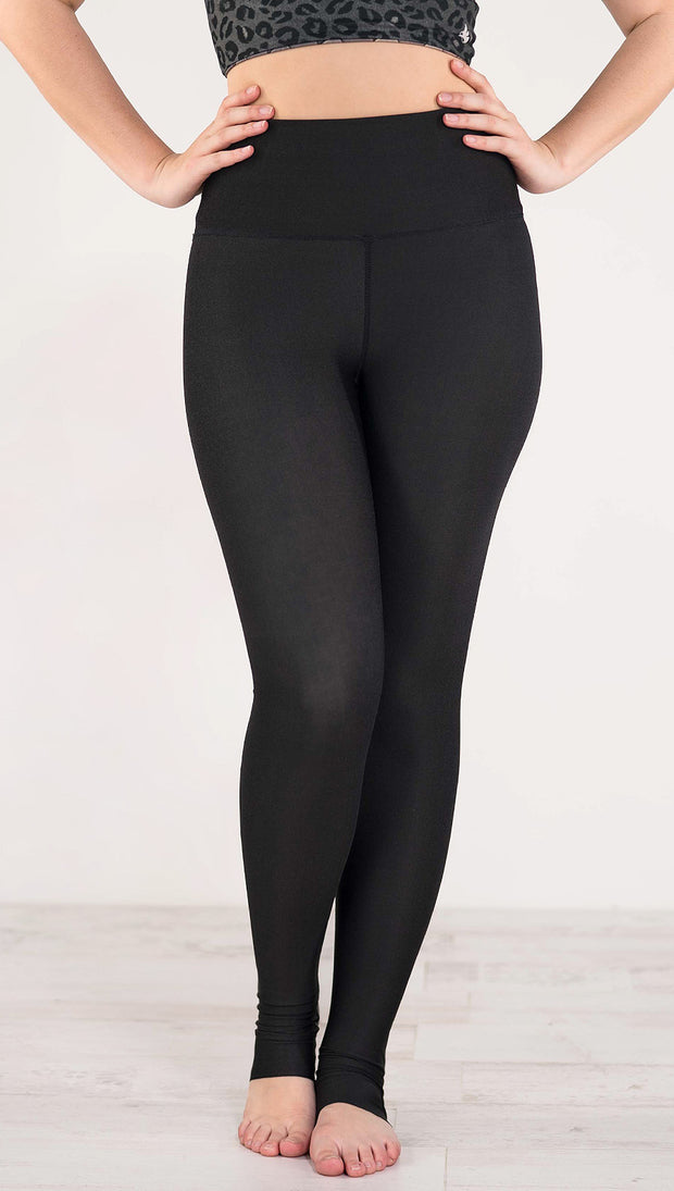 Front view of model wearing the reversible charcoal leopard leggings in the reversed all black side showing