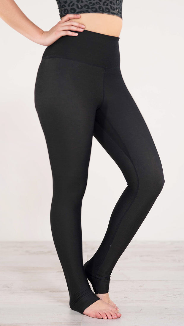Right side view of model wearing reversible charcoal leopard athleisure leggings in the reversed all black side showing