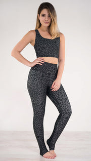 Front view of model wearing the reversible charcoal leopard print athleisure leggings in the colors gray and black