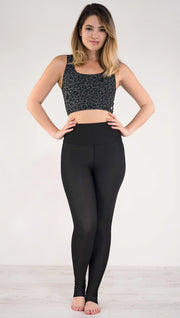 Front view of model wearing the reversible charcoal leopard print athleisure leggings in the reversed all black side showing