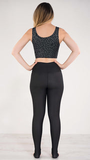 Back side view of model wearing the reversible charcoal leopard athleisure leggings in the reversed all black side showing