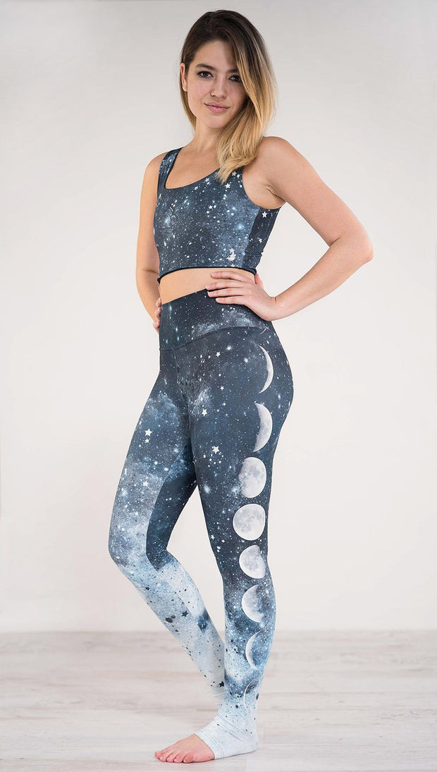 Left side view of model wearing blue full length athleisure leggings that fade to white with different moon phases in a vertical direction and tiny white stars across the leggings