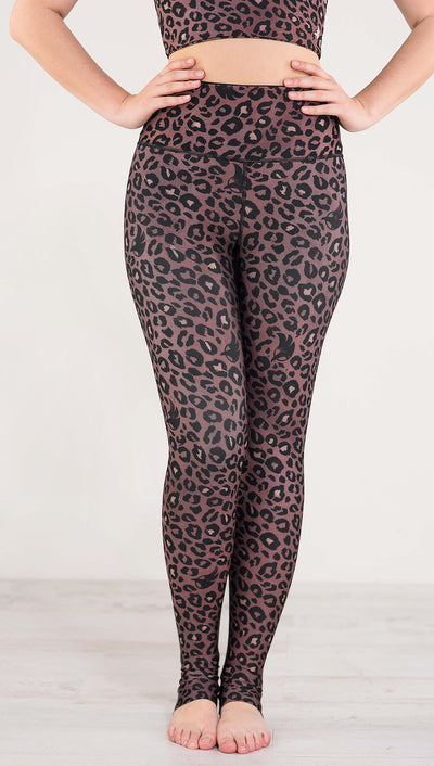 Front view of model wearing reversible red leopard print athleisure leggings in the colors dusty red and black