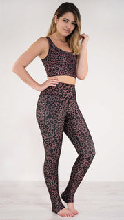 Right side view of model wearing the reversible red leopard print athleisure leggings in the colors dusty red and black