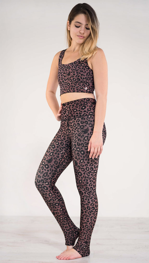 Left side view of the model wearing the reversible red leopard print athleisure leggings in the colors dusty red and black