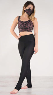 Left side view of model wearing the reversible red leopard athleisure leggings in the reversed all black side showing