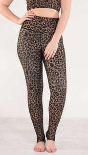 Front view of model wearing reversible tan leopard print athleisure leggings in the colors tan and black