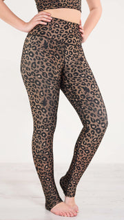 Right side view of model wearing the reversible tan leopard print athleisure leggings in the colors tan and black