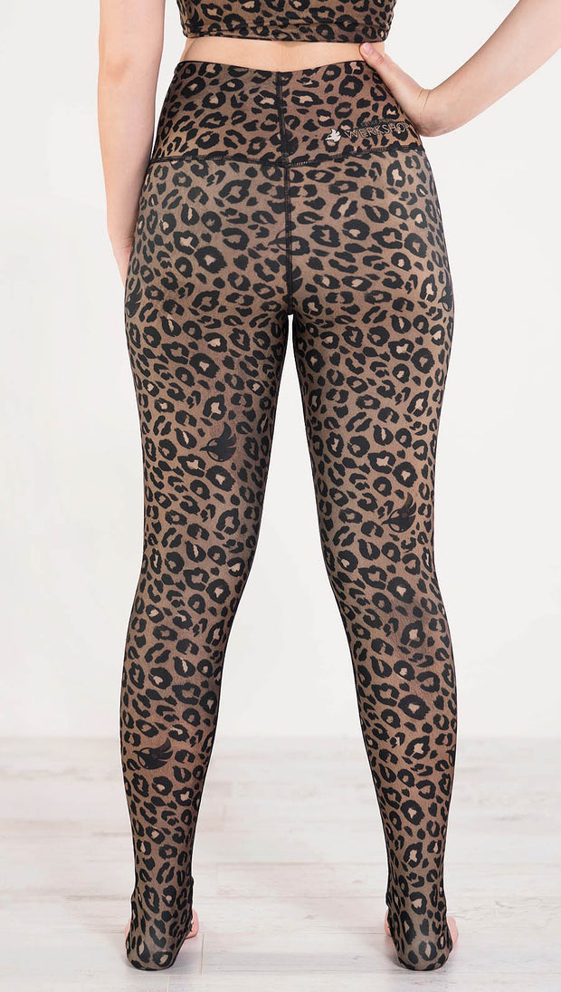 Back side view of model wearing the reversible tan leopard print athleisure leggings in the colors tan and black