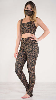 Left side view of model wearing the reversible tan leopard print athleisure leggings in the colors tan and black