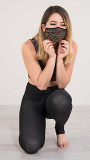 Model crouching wearing the reversible tan leopard athleisure leggings in the reversed all black side showing