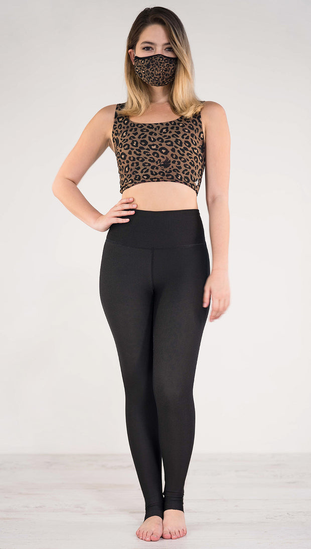 Front view of model wearing the reversible tan leopard athleisure leggings in the reversed all black side showing