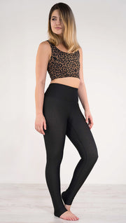 Right side view of model wearing the reversible tan leopard athleisure leggings in the reversed all black side showing