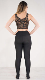 Back side view of model wearing the reversible tan leopard athleisure leggings in the reversed all black side showing
