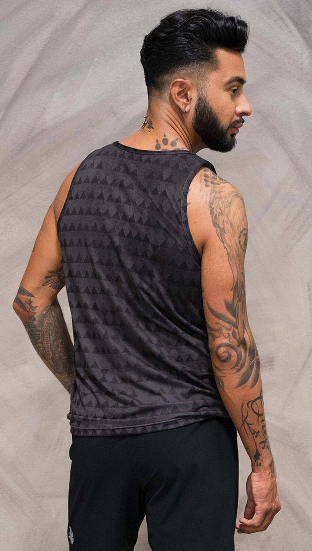 Close up back view of model wearing charcoal black printed tank top with distressed tribal inspired art
