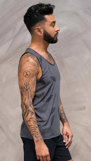 Close up right side view of model wearing gray tank top with vilva leaf inspired art