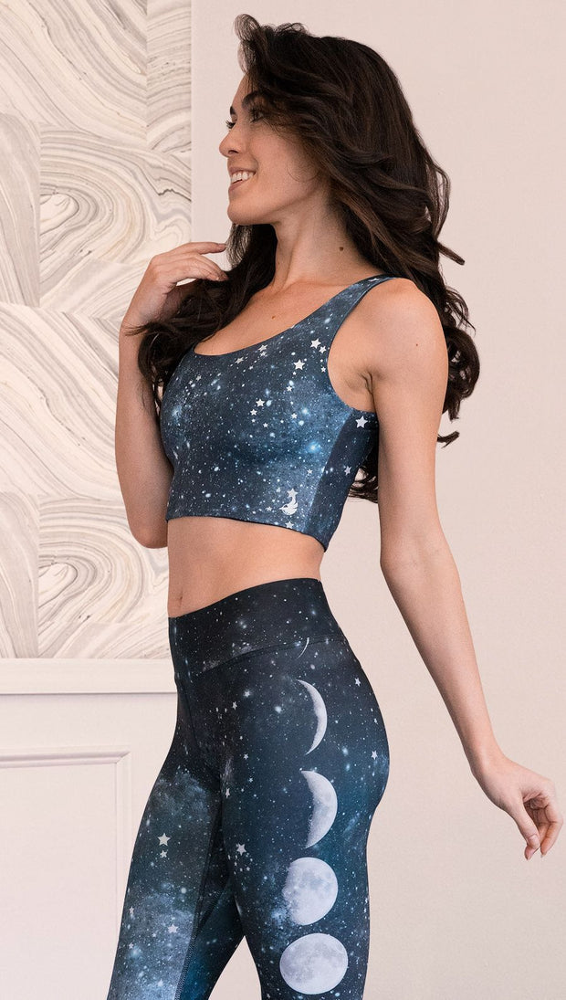 closeup left side view of model wearing reversible tank top with starry night/galaxy sky on one side and a black ombre brushstroke print on the reverse side.