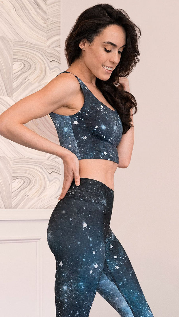 closeup right side view of model wearing reversible tank top with starry night/galaxy sky on one side and a black ombre brushstroke print on the reverse side.