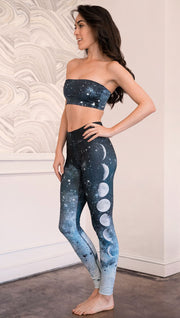 left side view of model wearing reversible bandeau with starry night/galaxy sky on one side and a black ombre brushstroke print on the reverse side