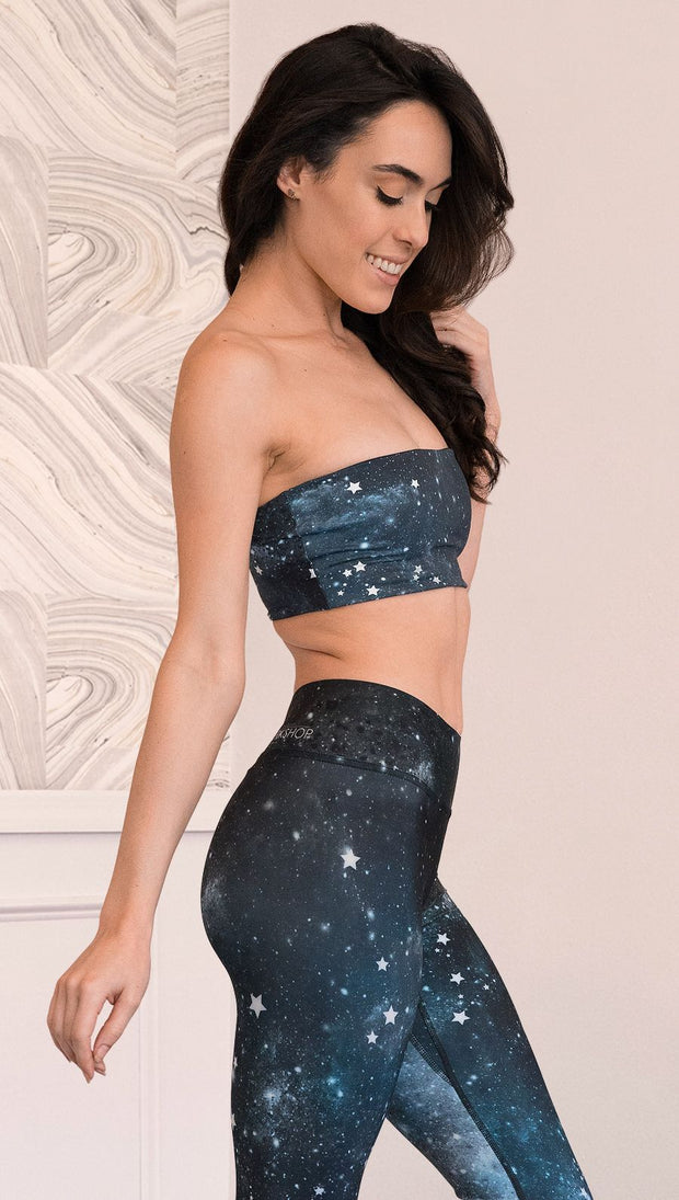 closeup right side view of model wearing reversible bandeau with starry night/galaxy sky on one side and a black ombre brushstroke print on the reverse side