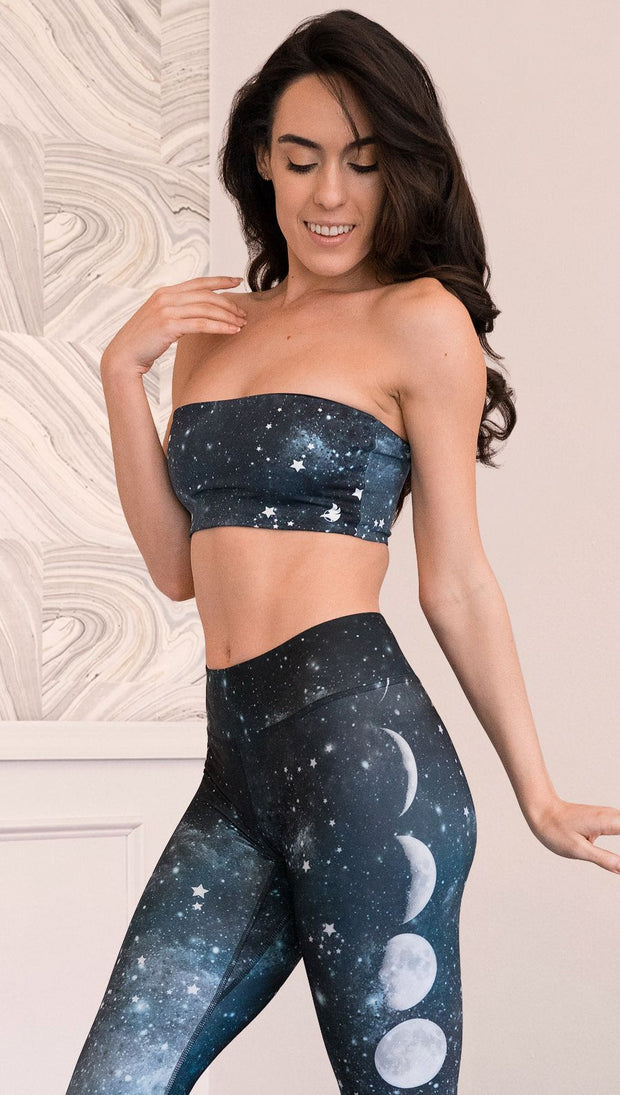 closeup front view of model wearing reversible bandeau with starry night/galaxy sky on one side and a black ombre brushstroke print on the reverse side