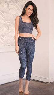 Front view of model wearing mosaic printed capri leggings with moon artwork on left hip